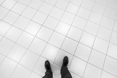 Photo pour Male feet stand on office floor with white shining square tiling - image libre de droit