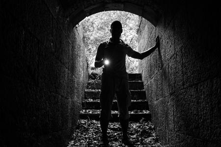 Foto de Young man with a flashlight enters the stone tunnel and looks in the dark, monochrome photo - Imagen libre de derechos
