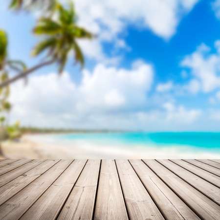 Photo pour Empty wooden pier background over blurred tropical beach coastal landscape with palm tree, cloudy sky and bright sea water - image libre de droit
