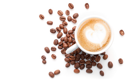 Foto de Small cup of cappuccino with coffee beans and heart shaped milk foam, top view isolated on white background - Imagen libre de derechos