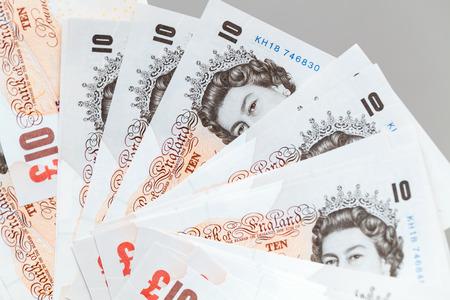 Foto de Ten pound notes of the Bank of England. Close-up photo over gray background with selective focus - Imagen libre de derechos