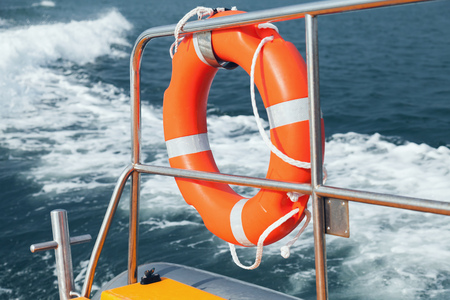 Foto per Red lifebuoy hanging on stern railings of fast motor boat - Immagine Royalty Free