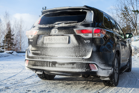 Photo for Saint-Petersburg, Russia - February 25, 2018: Black Toyota Highlander car stands on a roadside in winter season,  rear view - Royalty Free Image