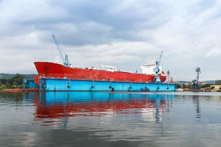 Foto per Red tanker is under repairing in blue dry dock of Varna shipyard, Bulgaria - Immagine Royalty Free