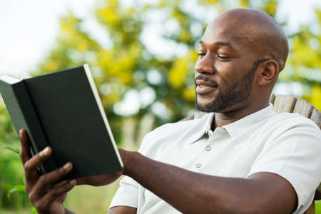 Photo pour Handsome African American man in his late 20s reading a book at the park on a summer day - image libre de droit