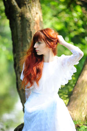Young red-haired pretty woman on the summer park