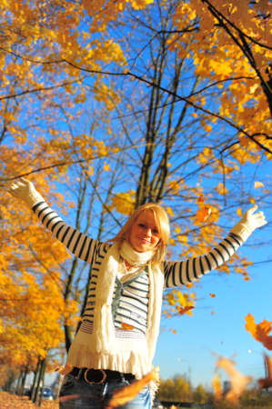 Portrait of a happy woman playing with autumn leaves