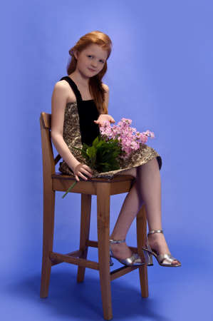 Red-haired girl sitting on a high chair
