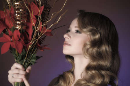 Vintage attractive blonde woman with a Christmas flower