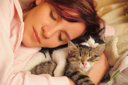 beautiful young woman sleeps with cats