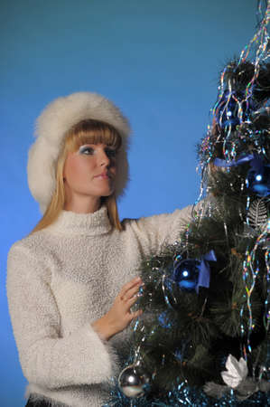 Beautiful blonde in fur hat and Christmas tree