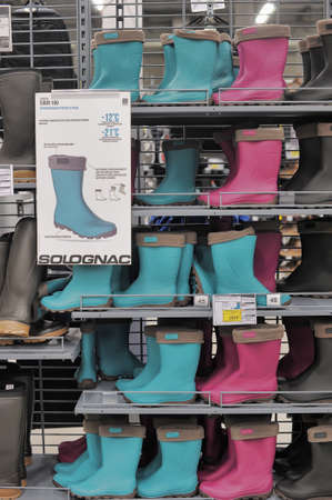 Diferent bright waterboots are on the shop shelves.