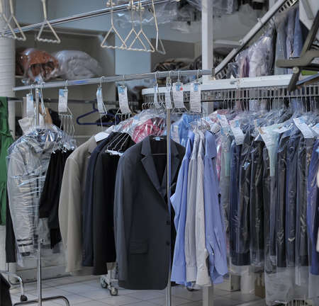 Photo for Reception point of dry cleaning, lot of clean clothes in pack. Auchan, St. Petersburg, Russia. - Royalty Free Image