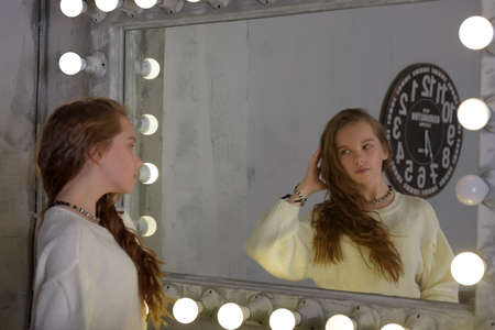 Photo for Portrait of a girl in a white sweater in the backlit mirror - Royalty Free Image