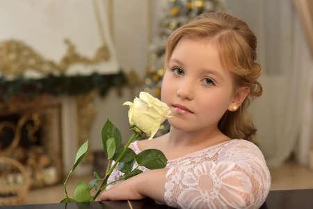 Foto de portrait of a teen blonde with a white rose in a lace blouse - Imagen libre de derechos