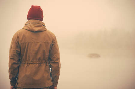 Foto de Young Man standing alone outdoor with foggy scandinavian nature on background Travel Lifestyle and melancholy emotions concept film effects colors - Imagen libre de derechos