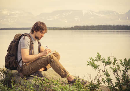 Photo pour Young Man Traveler with backpack reading book and writing notes outdoor mountains on background Summer vacations and Lifestyle concept - image libre de droit