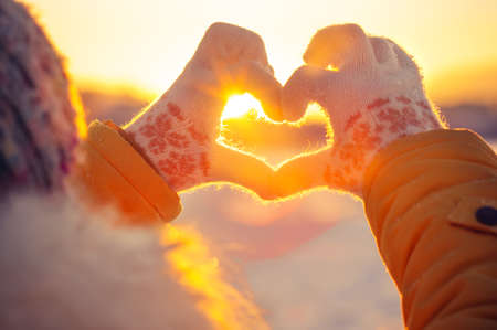 Foto de Woman hands in winter gloves Heart symbol shaped Lifestyle and Feelings concept with sunset light nature on background - Imagen libre de derechos