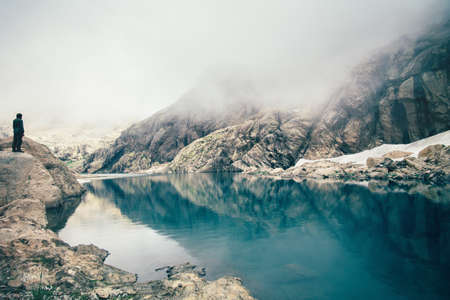 Photo pour Man Traveler standing alone on cliff lake and foggy mountains on background Travel Lifestyle inspiring concept outdoor - image libre de droit