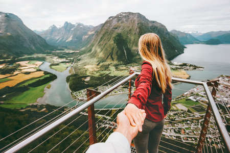 Photo pour Couple Man and Woman follow holding hands in Norway mountains Love and Travel happy emotions Lifestyle concept. Young family traveling active adventure vacations Rampestreken aerial view - image libre de droit