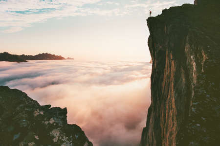 Photo pour Traveler man standing on the edge cliff over clouds sunset mountains travel adventure lifestyle journey vacations in Norway - image libre de droit