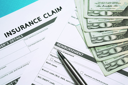 Foto de Insurance concept with insurance claim form and money - Imagen libre de derechos