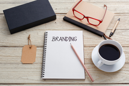 Foto de Branding concept with notebook, brand tag, product box , glasses and coffee cup on work desk - Imagen libre de derechos