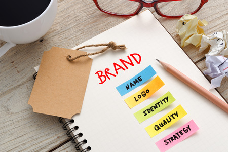 Foto de Brand marketing concept with notebook, brand tag and coffee cup on office desk - Imagen libre de derechos