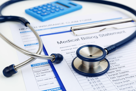 Photo for Stethoscope on medical bills and health insurance claim form - Royalty Free Image