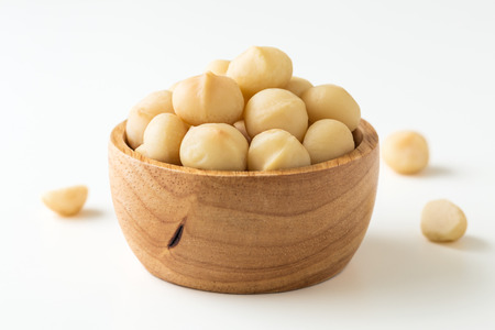 Photo for Macadamia nuts in wooden bowl on white background - Royalty Free Image