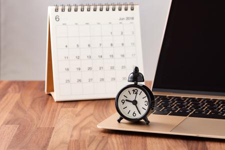 Foto de Time management concept with calendar and clock on computer on wooden table - Imagen libre de derechos