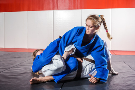 Photo for A young woman in a kimono makes a painful reception. Judo, jujitsu. Tatami, gym - Royalty Free Image