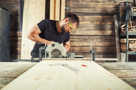 Photo for A man builder saws a board with a circular saw in the workshop - Royalty Free Image