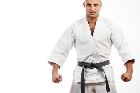 Photo for Young athletic man in white kimono for sambo, judo, jujitsu posing, looking straight, position of fighting post, hands clasped in fist - Royalty Free Image