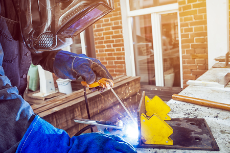 Photo for Man welder wearing a welding mask, building uniform and blue protective gloves brewing a metal welding machine on a street in a summer day, in the background an old brick building with a window and tools - Royalty Free Image