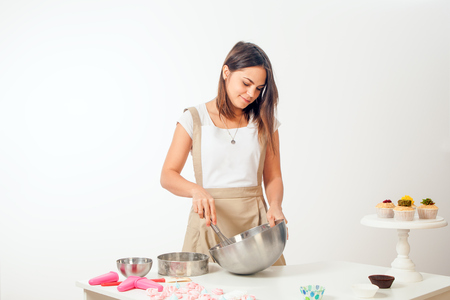 Foto de A young dark-haired female confectioner in a white T-shirt and in a beige apron    in a metal bowl, on the table stand a capcake on a white background - Imagen libre de derechos