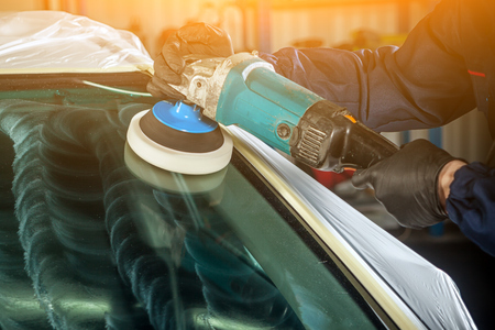 Foto de Close-up of a male mechanic with a blue prism and protective gloves polishes the front glass of the car with a modern green polishing machine from minor scratches after installation - Imagen libre de derechos