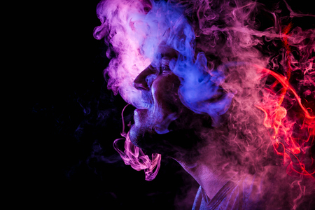 Photo pour Man  is admiting puffs of steam from the electronic cigarette, cloud of colored smoke of red and pink color on a black isolated.  Harm to smoking on the example of a young mugger  - image libre de droit