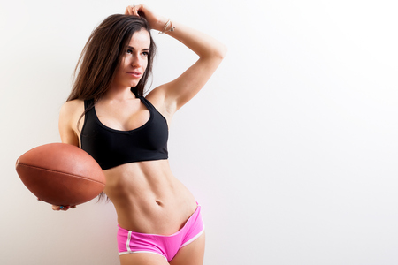 Photo pour Young attractive athletic woman in sports black T-shirt and pink shorts demonstrates her press and holds in her hand a rugby ball against white isolated background - image libre de droit