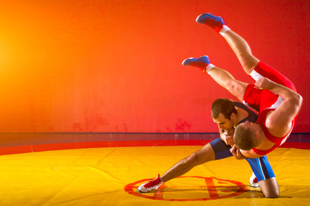 Photo pour Two young men in blue and red wrestling tights are wrestlng and making a hip throw on a yellow wrestling carpet in the gym - image libre de droit