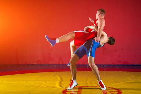 Foto de Two greco-roman  wrestlers in red and blue uniform wrestling   on a yellow wrestling carpet in the gym - Imagen libre de derechos