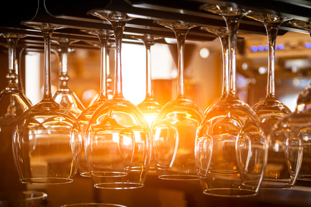 Foto de Beautiful new glasses for wine from glass hang in fastenings in even rows on a wooden table in a bar - Imagen libre de derechos