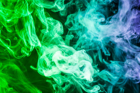 Photo for Colorful smoke of blue, green on a black isolated background. Background from the smoke of vape - Royalty Free Image