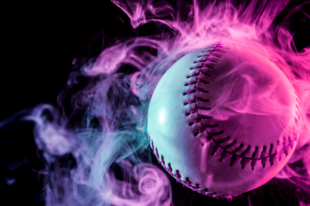 Foto de White baseball ball in multi-colored red smoke from a vape on a black isolated background - Imagen libre de derechos