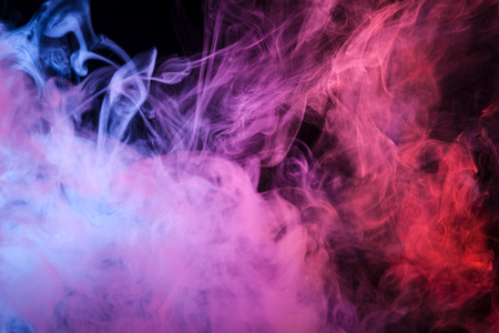 Photo pour Colorful pink,red and blue smoke  on a black isolated background. Background from the smoke of vape  - image libre de droit