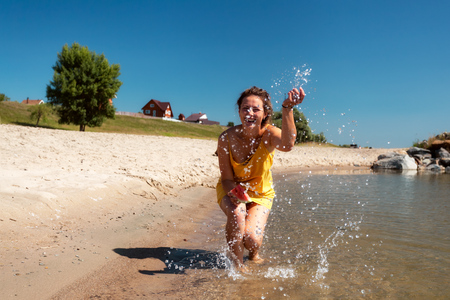 Photo for A cheerful dark-haired woman smiles, walks along the beach, kicks waves, sprays around a lot and enjoys the bright sun on a summer day. Concept of summer holidays at sea and live style - Royalty Free Image
