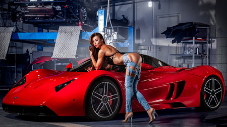 Foto per Novosibirsk, Russia - August  16, 2018: Young woman fitness model in jeans and a swimsuit posing for advertising a sports car of a supercar Marussia in a car salon - Immagine Royalty Free
