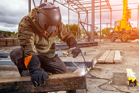 Foto de A strong man is a welder in brown uniform, welding mask and welders leathers, a metal product is welded with a arc welding machine at the construction site, blue sparks fly to the sides - Imagen libre de derechos