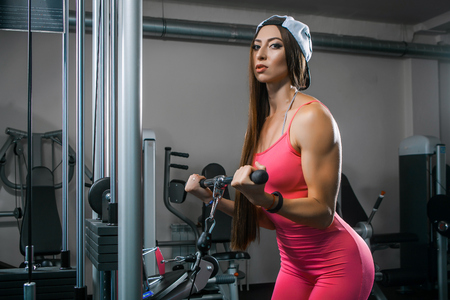Foto per Dark-haired woman athlete in a tracksuit shakes hands biseps on the simulator in the gym. Woman trainer shows how to shake hands for women - Immagine Royalty Free