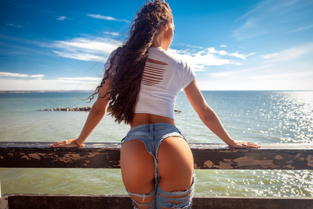 Foto de Summer concept. Holiday travel. Ideal woman's butt and hips - perfect anti-cellulite and skin care therapy program. Ocean beach photo. - Imagen libre de derechos
